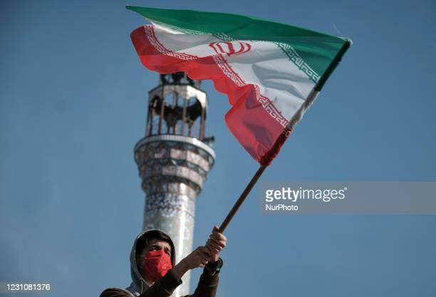 An Iranian man wearing a protective face mask waves an Iran flag while attending a rally to commemorate the 42nd Victory anniversary of the Islamic...