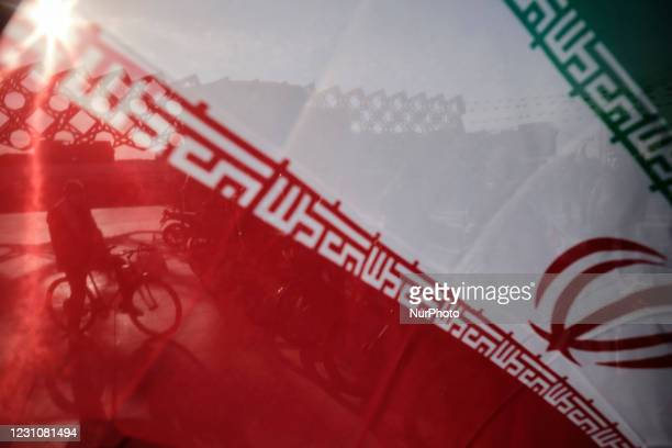 An Iranian man with his bicycle behind an Iran flag during a rally to commemorate the 42nd Victory anniversary of the Islamic Revolution, that held...