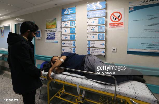 An Iranian man wounded in a stampede that broke out at the funeral of Revolutionary Guards commander Qasem Soleimani lies on a bed at Bahonar...