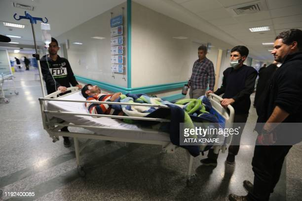 An Iranian man wounded in a stampede that broke out at the funeral of Revolutionary Guards commander Qasem Soleimani is wheeled into a room at...
