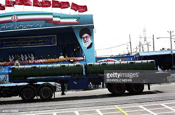 An Iranian military truck carries a Bavar373 air defence missile system past a portrait of Iran's supreme leader Ali Khamenei during the Army Day...