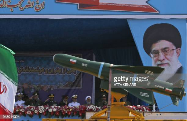 An Iranian military truck carries missiles past a portrait of Iran's Supreme Leader Ayatollah Ali Khamenei during a parade on the occasion of the...