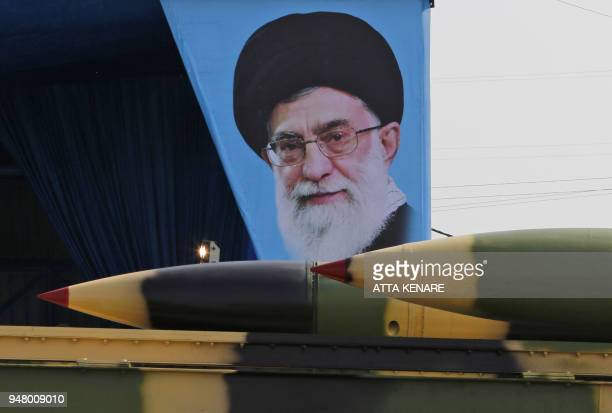 An Iranian military truck carries surfacetoair missiles past a portrait of Iran's Supreme Leader Ayatollah Ali Khamenei during a parade on the...