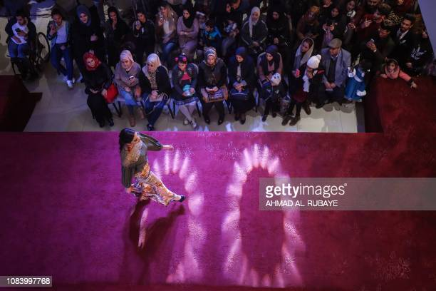 TOPSHOT An Iranian model presents an outfit designed by an Iranian female fashion designer during a show at a shopping mall in the Iraqi capital...