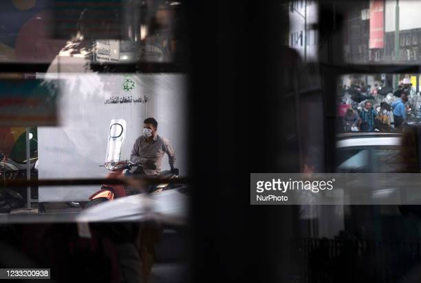 An Iranian motor taxi driver sits on his motorcycle in front of a banner that has located at a crossroad for electoral posters in downtown Tehran on...