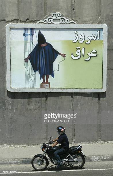 An Iranian motorist with the US flag on his helmet rides his motorbike past a mural depicting a scene from the torture of Iraqi prisoners by US...