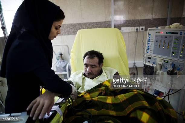 An Iranian nurse measures the blood pressure of a patient at the dialysis ward at the Helal Iran Clinic on March 11 2015 a day ahead of the World...