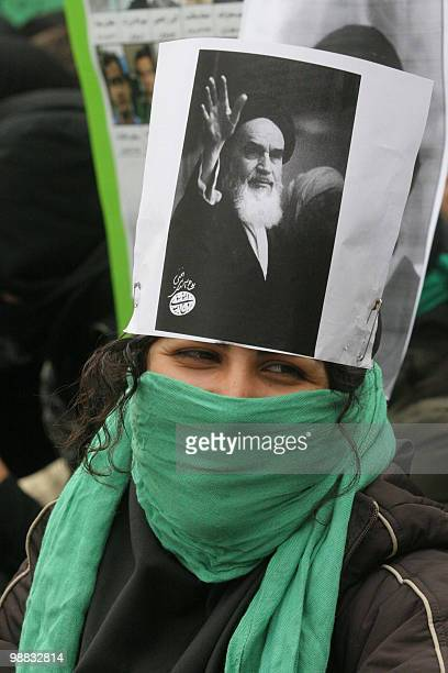 An Iranian opposition student covers her head with a picture of the late founder of the Islamic republic Ayatollah Ruhollah Khomeini and part of her...