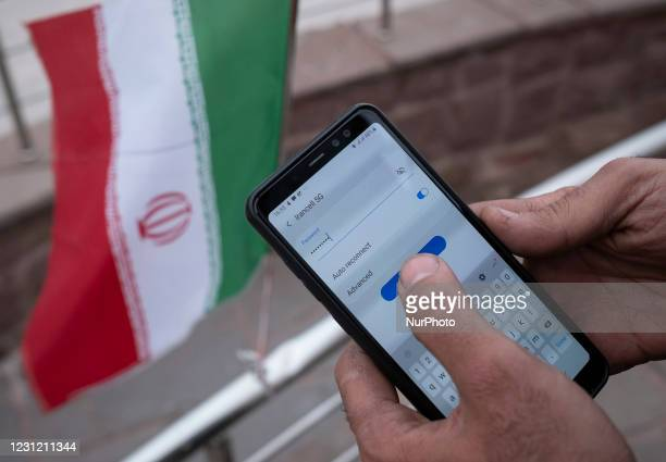 An Iranian park guard enters password on his smartphone as he tries to connect to an Irancell 5G network through the Huawei modem in northern Tehran...