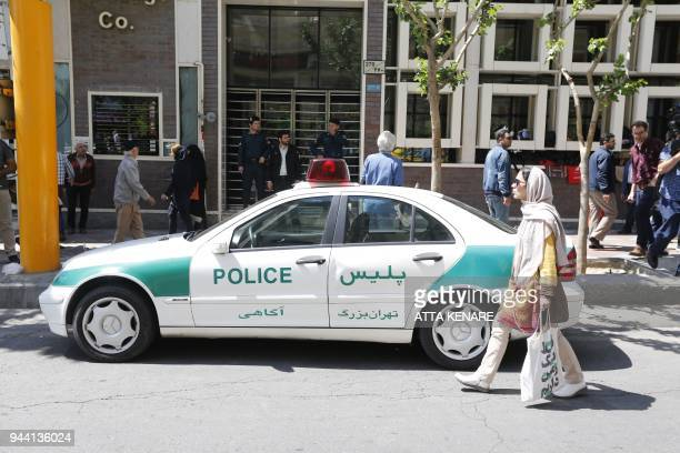 An Iranian police vehicle is seen parked outside a currency exchange shop in the capital Tehran on April 10 2018 Iran took the drastic step of fixing...