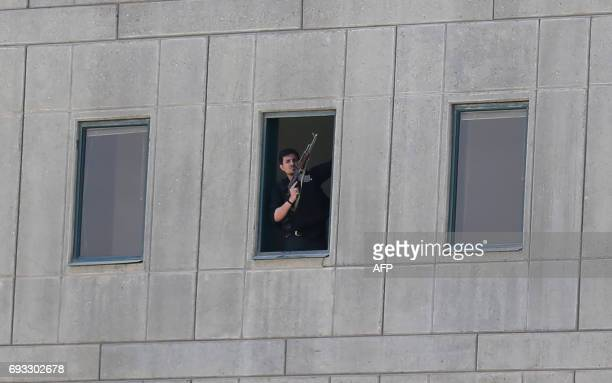 TOPSHOT An Iranian policeman holds a weapon as he stands by a window at the Iranian parliament in the capital Tehran on June 7 2017 during an attack...