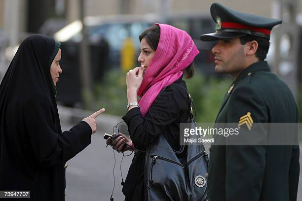 An Iranian policewoman warns a woman about her clothing and hair during a crackdown to enforce Islamic dress code on April 22 2007 in Tehran Iran...