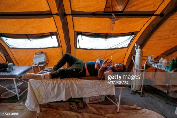 TOPSHOT An Iranian quake victim lies on an operating bed after receiving treatment at a field hospital in the town of Sarpole Zahab in the western...