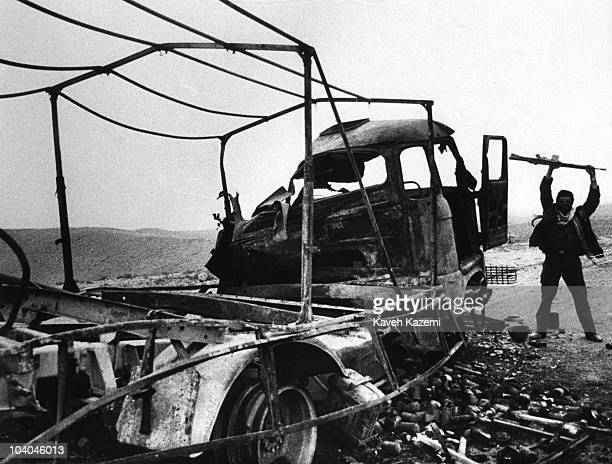 An Iranian Revolutionary Guard holds his rifle aloft in triumph over a burnedout Iraqi truck near Qasre Shirin Iran during the IranIraq War 13th...