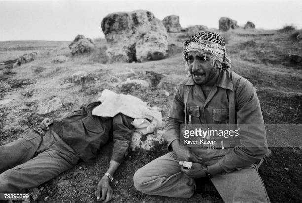 An Iranian Revolutionary Guard weeps by the body of his brother on Kooreh-Moosh height during heavy shelling by Iraqi forces at Sare Pole Zahab,...