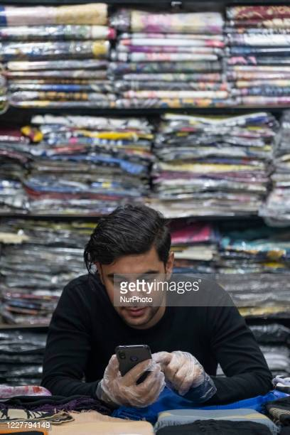 An Iranian salesman wearing protective gloves uses his smartphone as he sits at a shop in a bazaar near a shrine in the holy city of Qom 145Km south...