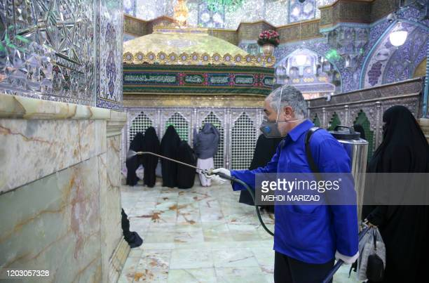 An Iranian sanitary worker disinfects Qom's Masumeh shrine on February 25, 2020 to prevent the spread of the coronavirus which reached Iran, where...