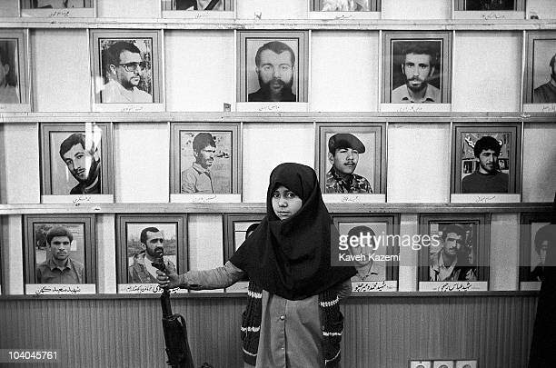 An Iranian schoolgirl in training as a member of the Basiji holding an automatic assault rifle in a Tehran mosque, 1st May 1988. Displayed on the...