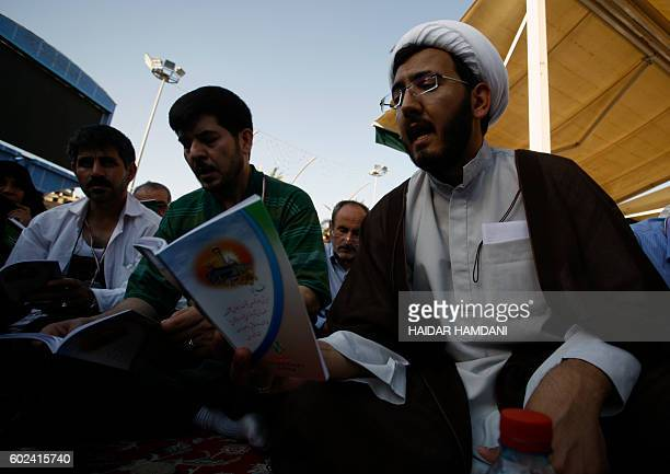 An Iranian Shiite Muslim cleric prays with fellow pilgrims in the holy Iraqi city of Karbala on Arafah day referring to a prayer performed by Shiites...