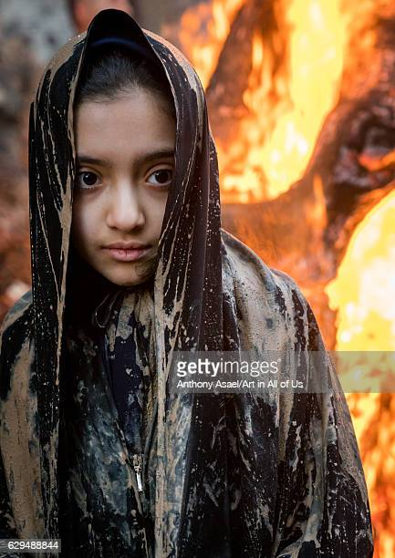 An Iranian shiite muslim girl stands in front a bonfire after rubbing mud on her chador during the Kharrah Mali ritual to mark the Ashura day...