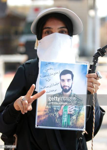An Iranian Shiite Muslim pilgrim holds a portrait and raises the victory gesture as she passes through Shalamijah border crossing in the southern...