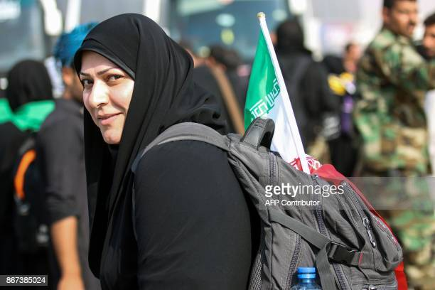 An Iranian Shiite Muslim pilgrim poses as she carries a national flag in her bag while passing through Shalamijah border crossing in the southern...