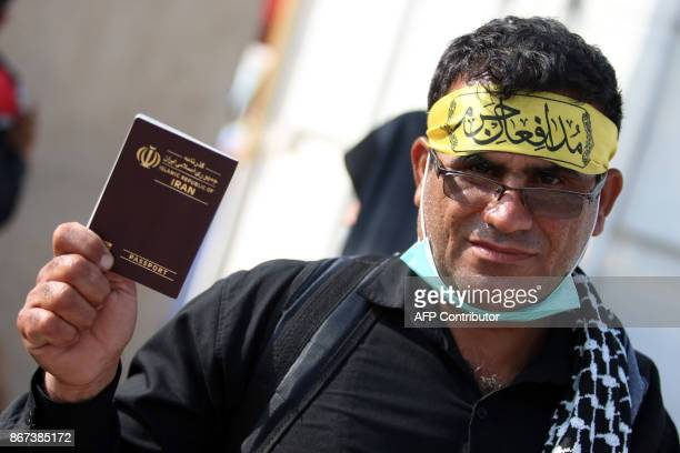 An Iranian Shiite Muslim pilgrims flashes his passport while passing through Shalamijah border crossing in the southern city of Basra on October 28...