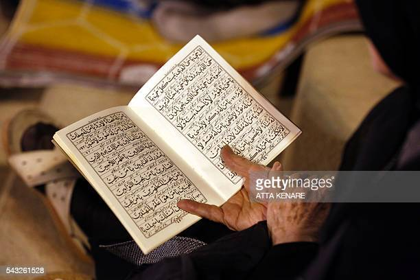 An Iranian Shiite Muslim woman holds a copy of the Koran Islam's holy book at the Imam Khomeini grand mosque in the capital Tehran in the early hours...