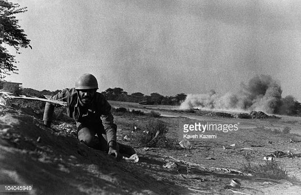 An Iranian soldier keeps low during heavy shelling by Iraqi artillery on the Zolfaghari front during the IranIraq War Abadan Iran 10th December 1980