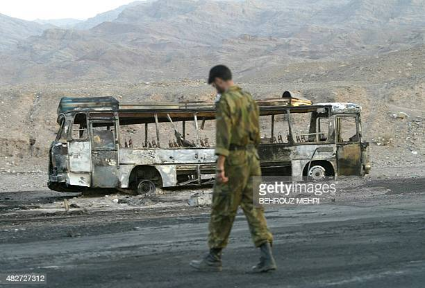 An Iranian soldier passes a burnt bus at the Nosrat Abad polic post 115km west of the southeastern border town of Zahedan 25 June 2004 At least 90...