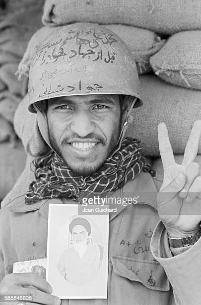 An Iranian soldier proudly displays a photo of Ayatollah Khomeini while signing the victory salute in a bunker during the 1980 IranIraq War