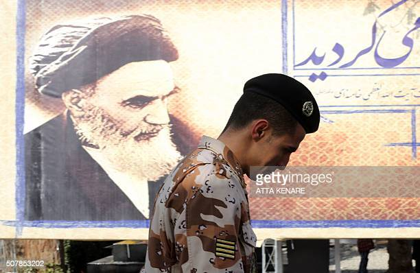 An Iranian soldier walks past a giant board displaying a portrait of the late founder of the Islamic Revolution Ayatollah Ruhollah Khomeini as...