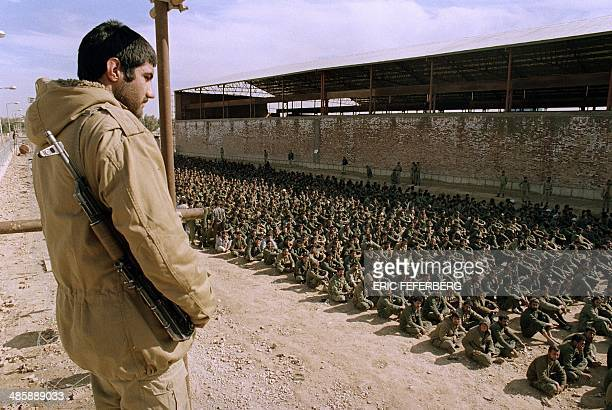 An Iranian soldier watches over some Iraqi POW 22 January 1987 in a camp in Ahvaz some 100 km north of Abadan Iraqi soldiers were captured in the...