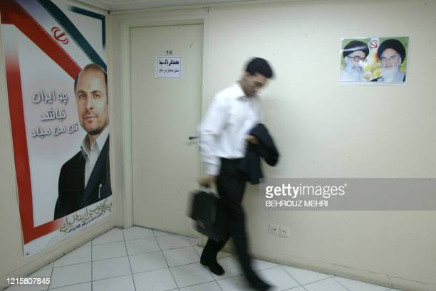 An Iranian staff of the headquarter of Iranian candidate Mohammad Baqer Ghalibaf a populist former national police chief passes by his poster and...