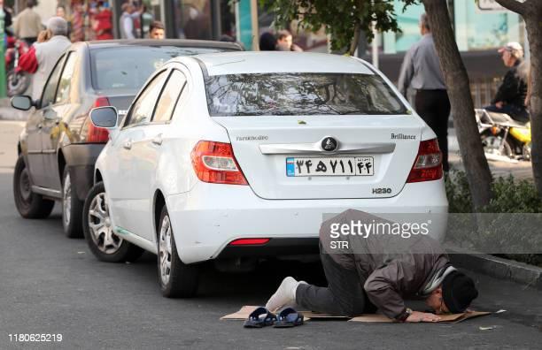 An Iranian street vendor performs the noon prayer on a side street in the Islamic republic's capital Tehran on November 7 2019 Iran resumed uranium...