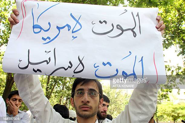 An Iranian student holds up a sign that reads 'death to American death to Israel' as he attends an antiIsraeli demonstration in front of the United...