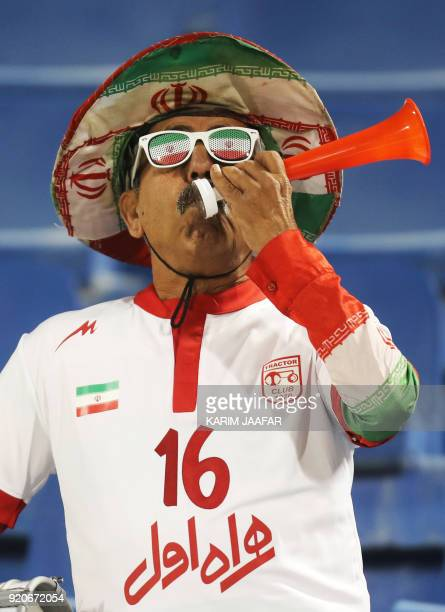 An Iranian supporter watches the AFC Champions League Group A football match between Qatar's AlGharafa and Tractor Sazi Tabriz of Iran at the Thani...