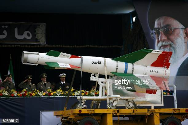 An Iranian surface to surface Ghasedak missile is driven past portraits of Iran's late founder of the Islamic Republic Ayatollah Ali khamenei during...