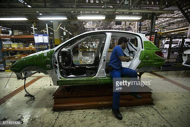 An Iranian technician works on a Peugeot 206 car at the Iran Khodro auto plant west of Tehran on February 20 2016 / AFP / BEHROUZ MEHRI