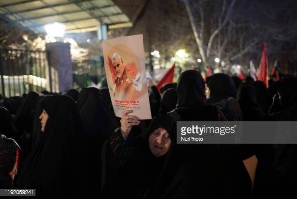 An Iranian veiled woman holds-up a portrait of Qasem Soleimani as she arrives to take part a mass funeral for the commander of the IRGS Qods Force...