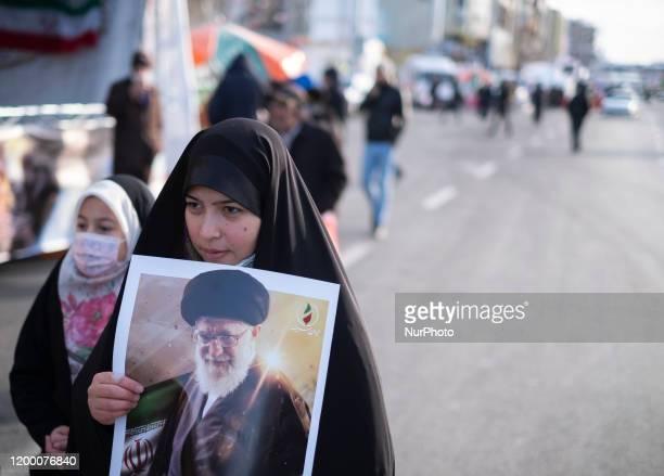 An Iranian veiled woman walks along the Azadi avenue as she carrying a portrait of Irans Supreme Leader Ayatollah Ali Khamenei during a rally to mark...