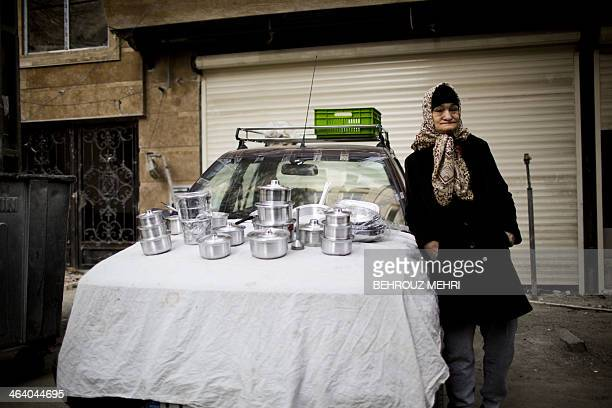 An Iranian vendor displays some kitchen utensils for sale in central Tehran on January 20 2014 Iran announced that it would halt production of 20...