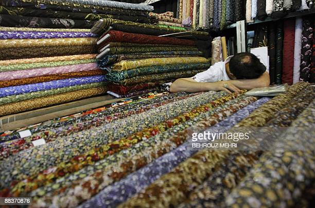 An Iranian vendor takes a nap on rolls of fabric at his shop at the Grand Bazaar of Tehran on June 9, 2009. Putting energy-rich Iran's derailed...