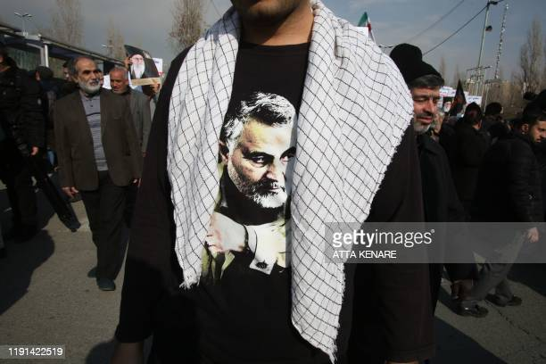 TOPSHOT An Iranian wearing a tshirt with a picture of slain commander Qasem Soleimani takes part in a demonstration in the capital Tehran on January...