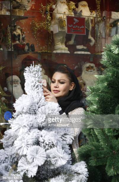 An Iranian woamn takes a picture of a Christmas tree on a street in the capital Tehran on December 24 on Christmas eve / AFP PHOTO / ATTA KENARE