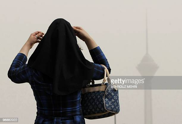 An Iranian woman adjusts her headscarf as smog covers the Milad telecommunications tower in northwestern Tehran on July 7 2009 Iranian opposition...
