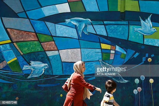 An Iranian woman and child walk past graffiti in downtown Tehran on April 27 2016 / AFP / ATTA KENARE