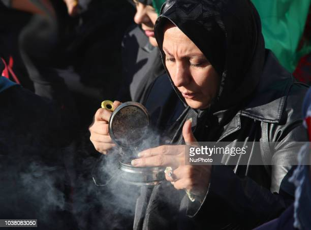 An Iranian woman carries incense to bless participants as Iranian Shiite Muslim mourners take part in a Muharram procession in Toronto Ontario Canada...