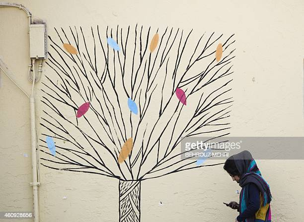 An Iranian woman checks on her mobile phone as she walks past graffiti of a tree on al wall in central Tehran on December 31 2014 AFP PHOTO/BEHROUZ...