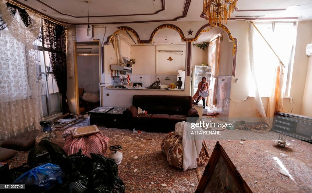 An Iranian woman collects items from an apartment in a damaged building in the town of Sarpol-e Zahab in the western Kermanshah province near the border with Iraq, on November 14, 2017, following a 7.3-magnitude earthquake that left hundreds killed and thousands homeless two days before. /